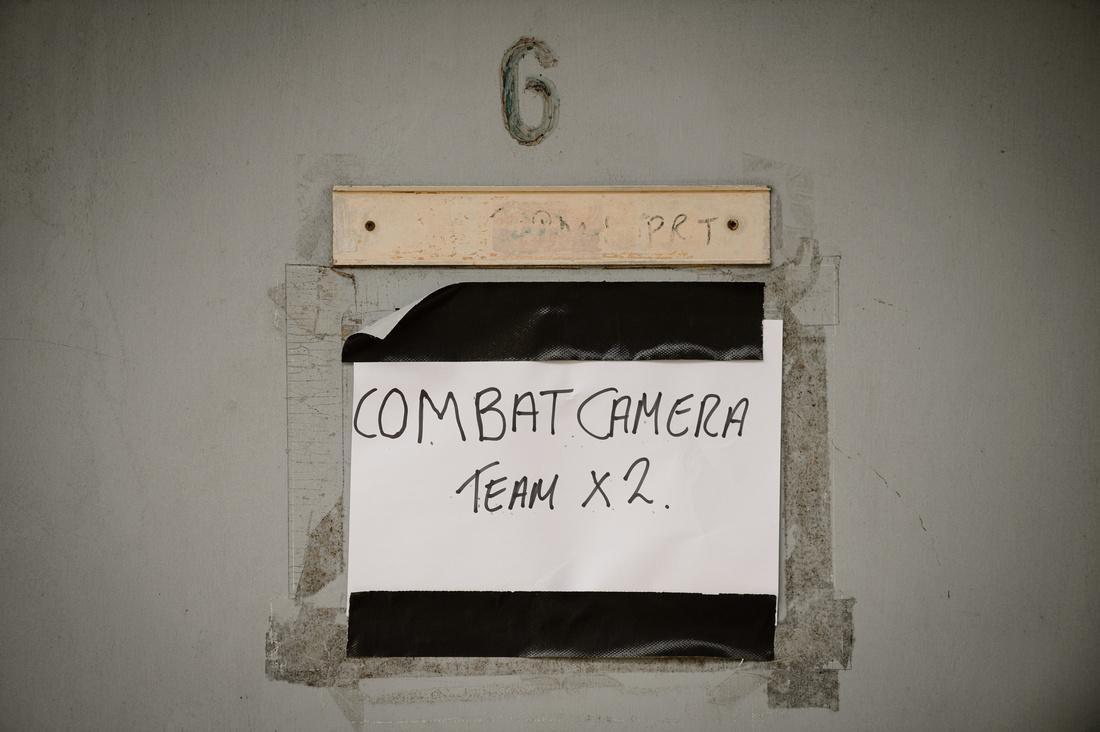 a paper sign saying Combat Camera team