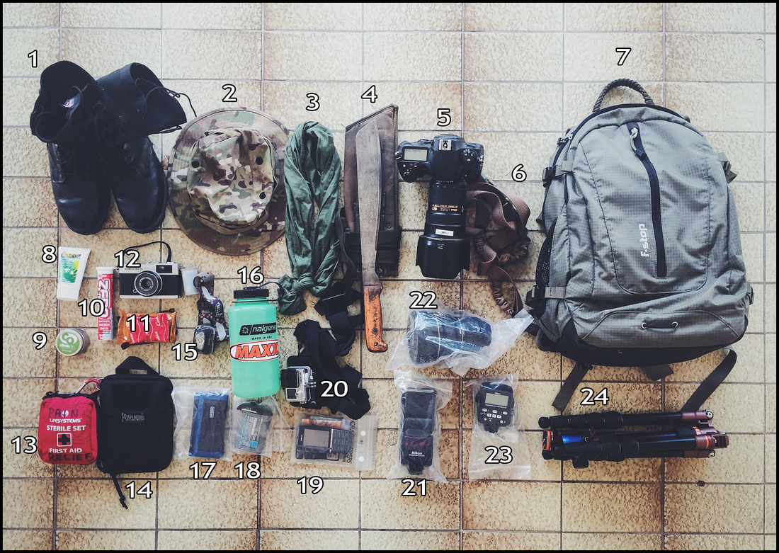 The contents of a camera bag on the floor that is taken into the jungles of Brunei.