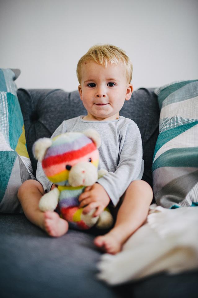 Young boy holds rainbow Teddy
